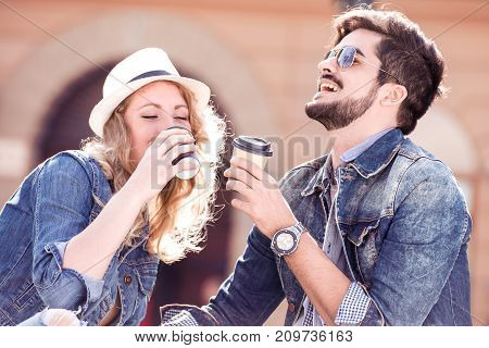 Young loving couple on a bench in the street sitting and holding coffee to go in the hands.