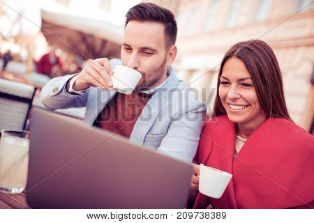 Happy couple sitting in street cafe together and using laptop, man drinking coffee.