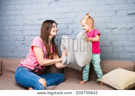Mom And Daughter Play On The Couch With Pillows Fight. Dressed In Bright Stylish Clothes In A Room
