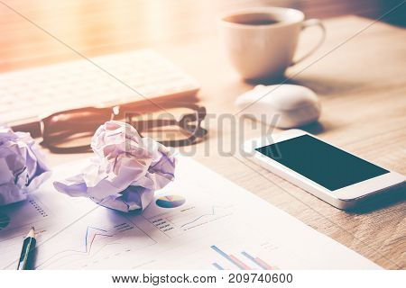 Business workplace with keyboard mouse and crumpled paper balls papers with graphs and diagrams for investment. Business and Investment Concept