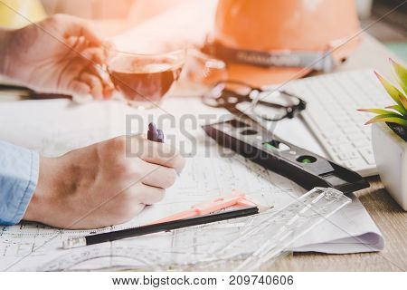 Top View Architect working on blueprint. Architects workplace. Engineer tools and safety control blueprints ruler orange helmetradiolaptop and divider compass. Construction Concept.