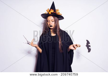 young sexy gothic woman in the image of a witch in halloween, in a big black hat, adorned with yellow leaves, looks sad