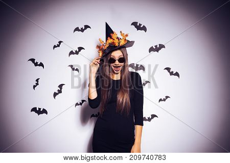A young sexy gothic woman in the shape of a witch in halloween, wearing sunglasses and a big hat, looks happily