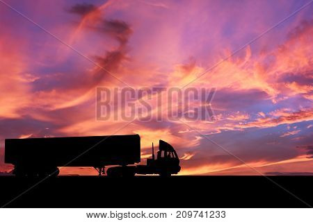 Trailer truck moving on the highway with amazing colorful sky.