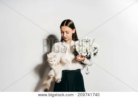 a young beautiful girl holds a big white bouquet of flowers and a white cat in her hands, and she does not like it because she has an allergy