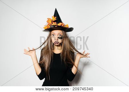 a young sexy gothic woman in the shape of a witch in halloween, in a big black hat, adorned with yellow leaves, looks sad