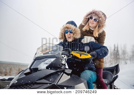Snowmobile. People girl and guy on the snowmobile laugh. Concept winter vacation.