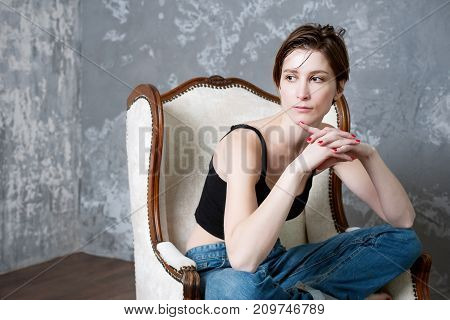 The girl in blue jeans sitting at studio in an armchair on a dark blue background