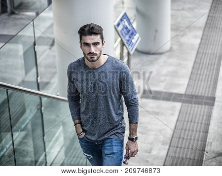 Handsome young man walking on stairway looking at camera