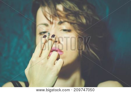 Abstract portrait of beautiful young girl with messy hair holding cigarette in her hand and looking at her selective with selective focus