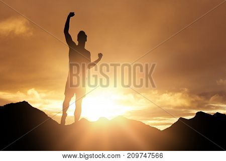 Male athlete posing after victory against cloudy sky landscape