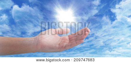 Cropped hand of woman offering against view of overcast against blue sky