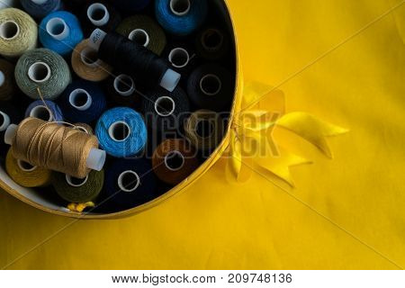 round box wrapped in a bow with coils of colored thread on a yellow background