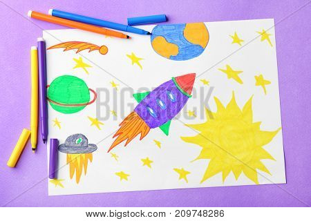 Child's drawing of rocket in space on violet background