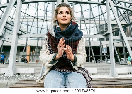 a girl with a big scarf sits on a bench in a city street and looks mysteriously away
