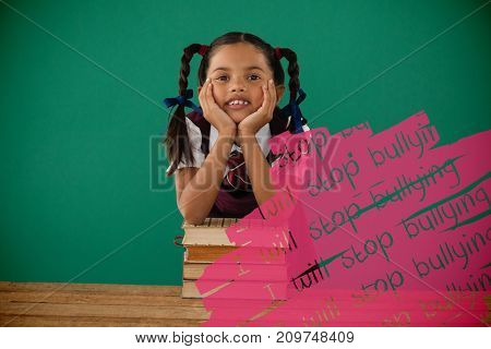 I will stop bullying text on black scribbling against schoolgirl leaning on books stack against chalkboard in classroom