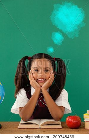 Digital composite image of blue spray paint against schoolgirl reading a book against green background