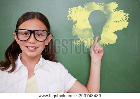 Cute pupil pointing against digital composite image of light bulb on black spray paint