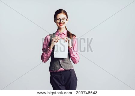 smiling red-haired girl with glasses holds a sheet of paper in her hands and looks into the camera