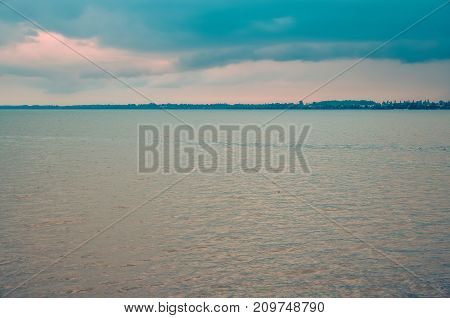 Minimalist summer landscape. Large lake with coastline on a cloudy day.