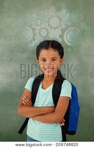 Digital composite image of white gears on blue spray paint against portrait of cute school girl standing with arms crossed