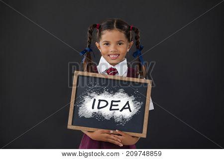 Digital composite image of idea text on black spray paint against portrait of schoolgirl holding blank slate against blackboard