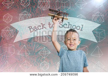 Portrait of boy holding toy airplane against back to school against green chalkboard