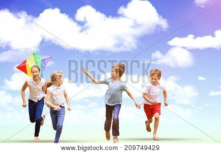 Full length of boy holding kite running with friends against blue sky