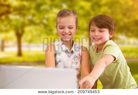 Siblings using digital tablet against trees in grassy landscape