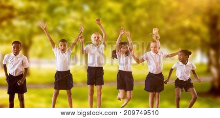 Full length of students in school uniforms jumping against trees in grassy landscape