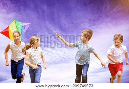 Full length of boy holding kite running with friends against view of cloudy sky