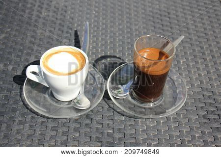 on the table is a glass with hot and strong coffee