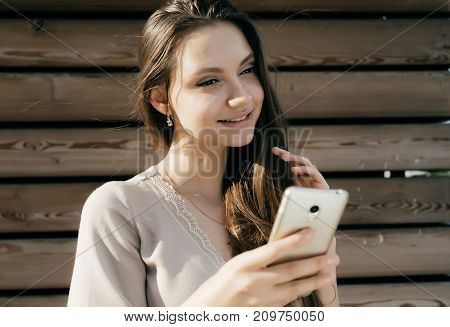 lovely girl stands on a wooden background and holds a phone in her hands and smiles