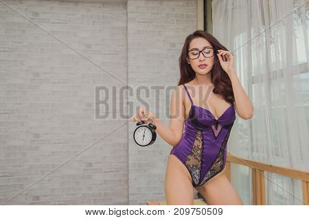 Sexy Women Doing Something With A Clock.