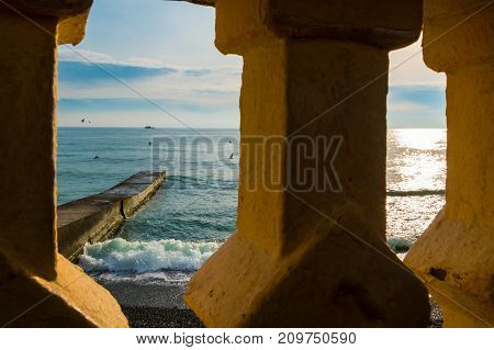 Concrete fence and sea with breakwater seen through it Sochi Russia