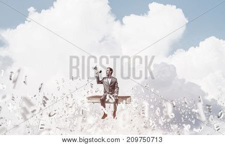 Young businessman sitting on books and screaming emotionally in megaphone