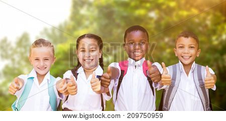 Portrait of students showing thumbs up sign against trees in the forest