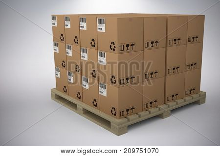 Cardboard boxes arranged on wooden pallet against grey background