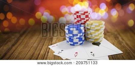 Tilt image of casino tokens with playing cards against wooden table
