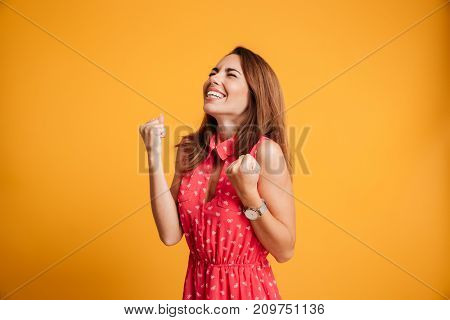 Close-up of emotional young celebrating woman with closed eyes keeping hands in fists, isolated on yellow background