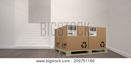 Cardboard boxes arranged on wooden pallet against staircase amdist wall