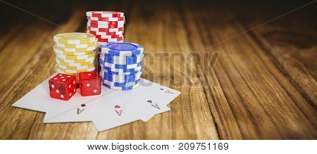 Tilt image of casino tokens with playing cards and dice against wooden table