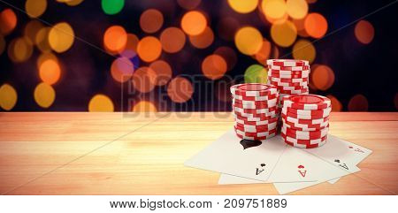 Playing cards with red casino tokens against composite image of brown parquet
