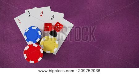 Overhead view of casino tokens with playing cards and dice against purple painted paper