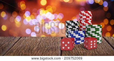 Red dice with stack of colorful casino tokens against composite image of table