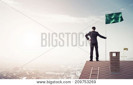 Businessman standing on house roof and holding flag. Mixed media