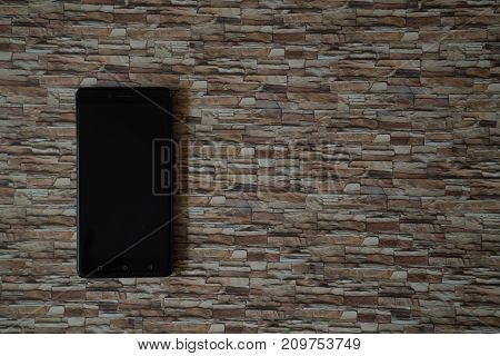 Switched off smartphone screen on stone facing background