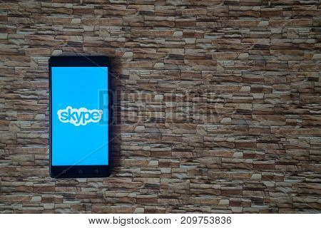 Los Angeles, USA, october 19, 2017: Skype logo on smartphone screen on stone facing background