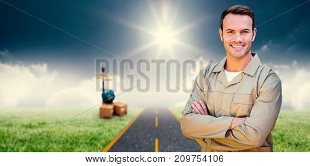Confident delivery man standing with arms crossed against road on grass