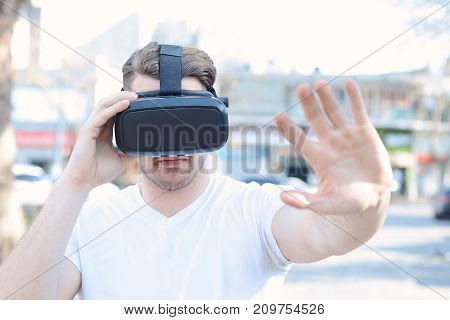 Young man using virtual reality glasses. Outdoors